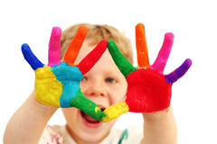 Happy child with painted hands. Five year old boy with hands painted in colorful paints ready for hand prints royalty free stock photo