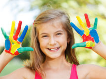 Happy child with painted hands. Ten year old girl with hands painted in colorful paints ready for hand prints royalty free stock photos