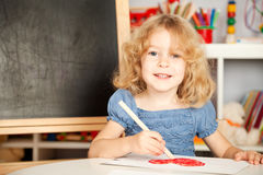 Happy child painting heart Stock Image