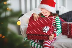 Happy child in pajamas with gifts on christmas morning near chr stock images
