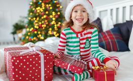 Happy child in pajamas with gifts on christmas morning near chr stock image