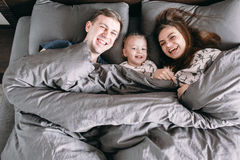 Happy child with parents in bed at home stock photos