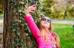 Happy child in park. selfie time. Natural beauty. Childhood happiness. summer nature. little girl make selfie in park. Spring holiday. Green environment stock images