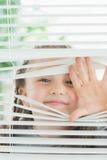 Happy child peeking through blinds. Happy child peeking through window blinds Stock Photo