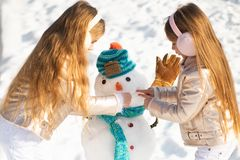 Happy child plaing with a snowman on a snowy winter walk. Making snowman and winter fun for children. Two little girl stock images