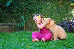 Happy child play and hug family pet - labrador puppy. Funny photo of happy baby hugging beautiful golden labrador retriever puppy. Girl play with dog. Family stock photos