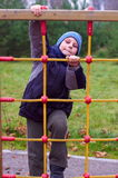 Happy child in playground climbing up playing Royalty Free Stock Photography