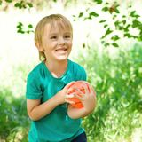 Happy child playing with ball outdoors. Little boy catching a small ball. Healthy and happy childhood. Funny child outdoors. Kids royalty free stock images