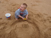 Happy child playing on the beach. Happy caucasian 3-year old child playing on the beach royalty free stock image