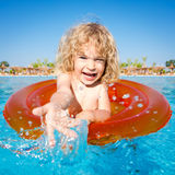 Happy child playing in blue water Stock Images