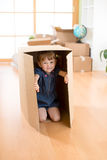 Happy child playing with boxes after moving in new house. Happy child plays with boxes after moving in new house royalty free stock image