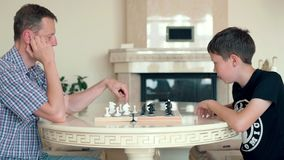 Happy child playing chess with a senior man at home. Family relationship with father and son. Play a board game stock footage