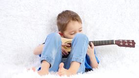 Happy child playing a children`s acoustic guitar, smiling, sitting on a white sofa. Music, parenting. 4k stock video