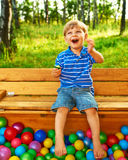 Happy child playing with colorful plastic balls Stock Photos