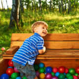 Happy child playing with colorful plastic balls Royalty Free Stock Image