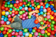 Happy child playing with colorful plastic balls Royalty Free Stock Photography