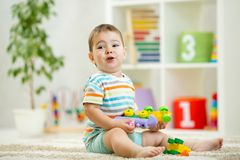 Happy child playing with colorful plastic bricks on the floor. Toddler having fun and building a train out of. Happy baby playing with colorful plastic bricks on Royalty Free Stock Images