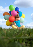 Happy child playing with colorful toy balloons outdoors royalty free stock photography