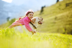 Happy child playing with dog. In green field Royalty Free Stock Photos