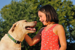Happy child playing with dog outside Stock Images
