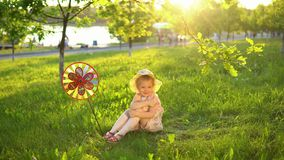 Happy child playing on grass under young oaks in a public park at sunset. stock video footage
