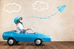 Funny kid driving toy car at home stock photography