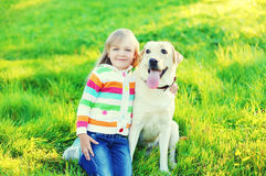 Happy child playing with labrador retriever dog on grass in summer Royalty Free Stock Photography