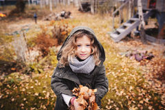 Happy child playing with leaves in autumn. Seasonal outdoor activities with kids. Lifestyle capture on the walk Stock Photo