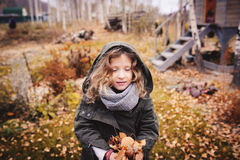 Happy child playing with leaves in autumn. Seasonal outdoor activities with kids. Lifestyle capture on the walk Royalty Free Stock Images