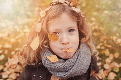 Happy child playing with leaves in autumn. Seasonal outdoor activities with kids Stock Photos