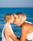 Happy child playing with mother. At the sea against blue sky background. Summer vacations Stock Photography