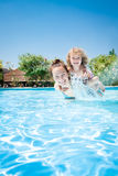 Happy child playing with mother in pool royalty free stock photos