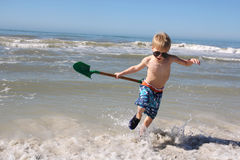 Happy Child PLaying in the Ocean Waves Stock Photos