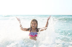 Happy child playing outdoors. Kid having fun in the sea. Summer Stock Photography