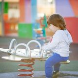 Happy child playing in the park on bouncing toys. Happy boy playing on the playground with his mother with metallic bouncing toys Stock Photo