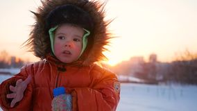 Happy child playing in the park on a sunny winter day. Snow winter landscape. on open air stock footage