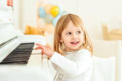 Happy child playing piano at modern class. Little girl at musical school. Education, skills concept. Preschool child learning to stock images