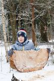 Happy child playing with piece of wood in the forest in winter royalty free stock images