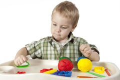 Happy child playing with plasticine. Colorful balls Royalty Free Stock Photos