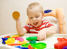 Happy child playing plasticine. Happy smiling child playing with plasticine Stock Photography