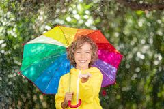 Happy child playing in the rain stock photography
