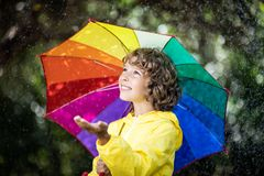 Happy child playing in the rain. Little girl with umbrella having fun outdoor in spring park stock photos