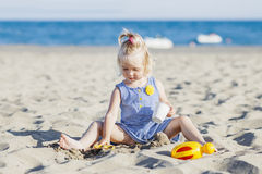 Happy child playing with sand at the beach in summer. Happy child, playing with sand at the beach in summer Stock Photos