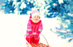Happy child playing with sled on snow in winter Stock Image