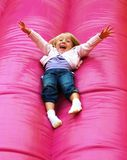 Happy child playing on slide. Happy little girl sliding down an inflatable bright pink slide Stock Photo