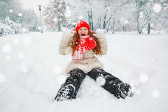 Happy child playing in snowing park. Stock Photos