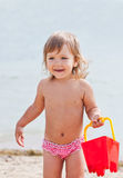 Happy child playing in the summer sea. With a red bucket stock photography