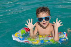 Happy child playing on the swimming pool at the day time. Stock Image