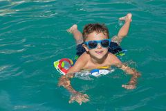 Happy child playing on the swimming pool at the day time. Royalty Free Stock Images