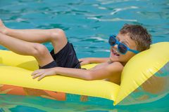 Happy child playing on the swimming pool at the day time. Stock Images